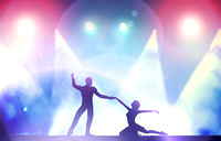 A couple of dancers in elegant, passionate dancing pose in club lights