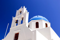 A white church with blue dome in Oia or Ia on Santorini island, Greece.