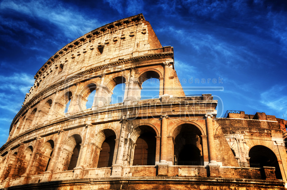 Colosseum in Rome, Italy. Amphitheatre over deep blue sky