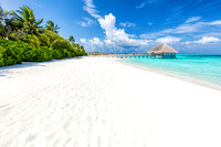 Wide sandy beach on a tropical island in Maldives. Palms and wat