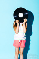 Little girl holding a vinyl disc against her head.