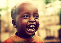 Poor young child laughing with tsetse insects on him. Tanzania, Africa
