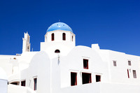 White buildings and church with blue dome in Oia or Ia on Santorini island, Greece