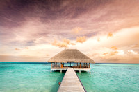 Wooden jetty leading to relaxation lodge. Maldives islands at sunrise