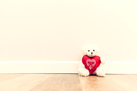 Cute teddy bear with big red plush heart. Sitting on wooden floor against white wall.
