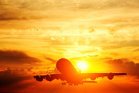 Airplane taking off at sunset. Silhouette of a flying passenger or cargo aircraft, airline