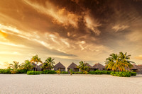 Beach and villas on an island in Maldives at sunset